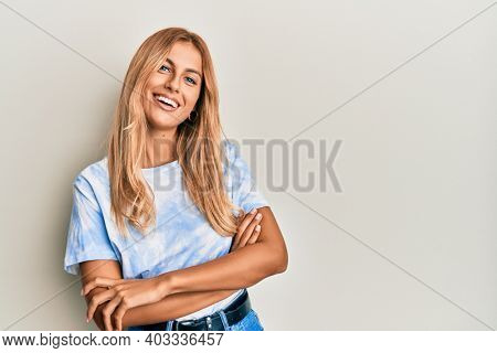 Beautiful blonde young woman wearing tye die tshirt happy face smiling with crossed arms looking at the camera. positive person.