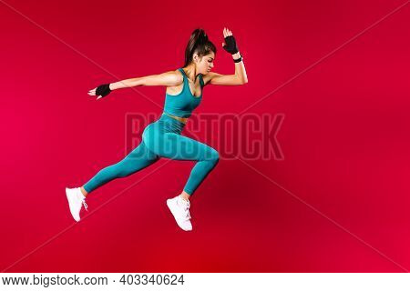 Sporty Woman Runner In Silhouette On Red Background. Photo Of Attractive Woman In Fashionable Sports