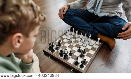 Intellectual Game. Little Thoughtful Boy Playing Chess With Grandfather While Sitting On The Floor I