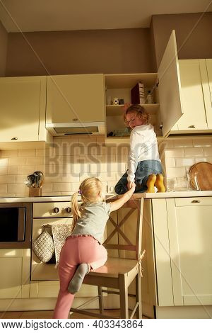 Little Naughty Boy Trying To Find Something Sweet In The Kitchen Cupboard Together With His Sibling