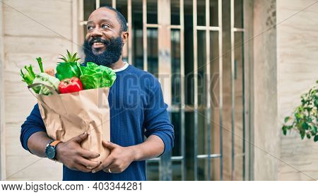 African american man with beard holding paper bag of groceries from supermarket