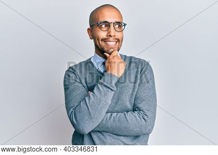 Hispanic adult man wearing glasses and business style with hand on chin thinking about question, pensive expression. smiling with thoughtful face. doubt concept.