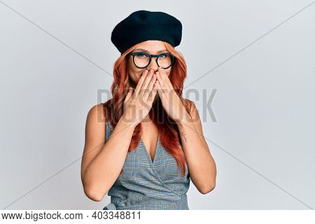 Young redhead woman wearing fashion french look with beret laughing and embarrassed giggle covering mouth with hands, gossip and scandal concept