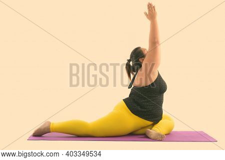 Studio Shot Of Young Fat Asian Woman Stretching Her Legs And Reaching Up While Doing Yoga Poses
