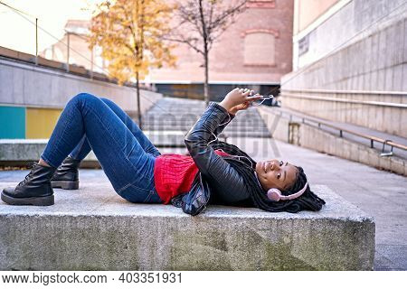 A Portrait Of A Smiling African-american Woman With A Cell Phone Is Chatting Or Listening To Music O