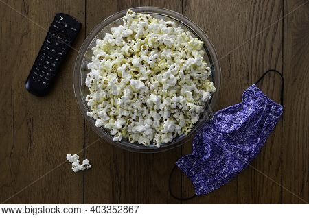 A Container With Popcorn A Control And A Mask