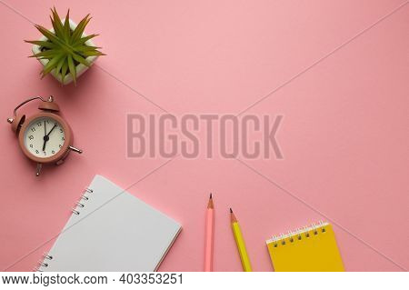Top View Office Table Desk. Workspace With Notepads, Pencils, Alarm Clock And Succulent Plant On Pin