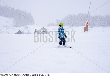 Downhill Skiing During A Heavy Snowfall. Child Skiing In Mountains. Active Kid With Safety Helmet, G