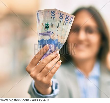 Young hispanic businesswoman smiling happy holding colombian 50 pesos banknotes at the city.