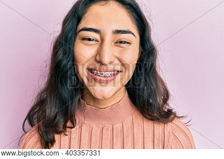 Hispanic teenager girl with dental braces showing orthodontic brackets looking positive and happy standing and smiling with a confident smile showing teeth