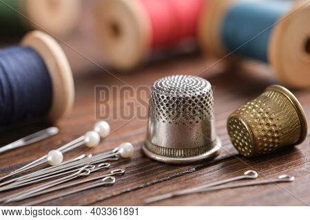 Two Thimbles And Including Pins. Various Wooden Spools Of Multicolored Threads On Background.