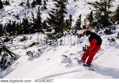 Guy In Bright Red Jumpsuit Rides Freeride On A Snowboard