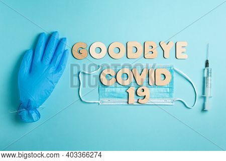 Words Goodbye Covid 19 From Wooden Letters And Syringe With Vaccine On A Blue Background, Inflated M