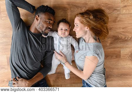 Top View A Multi Ethnic Baby Girl Surrounded Caring Parents Looks At Camera. A Multiracial Family Wi