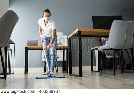 Female Janitor Mopping Floor In Face Mask In Office