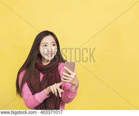 Happy Young Woman Holding Mobile Phone And Looking Up