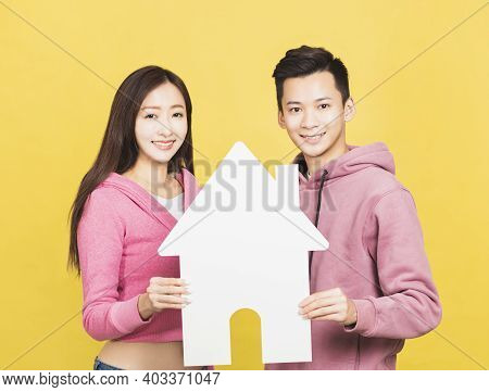 Happy Young Couple Holding A Small House The In Their Hands. Home And House Concept