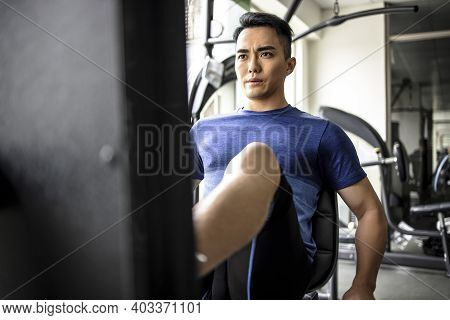 Asian Young Man Doing Leg Presses In Gym