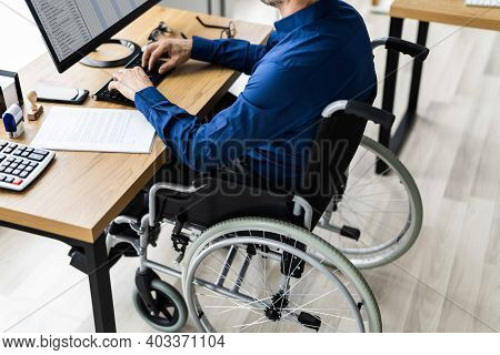 Disabled Handicapped Man In Wheelchair Working Using Computer Technology