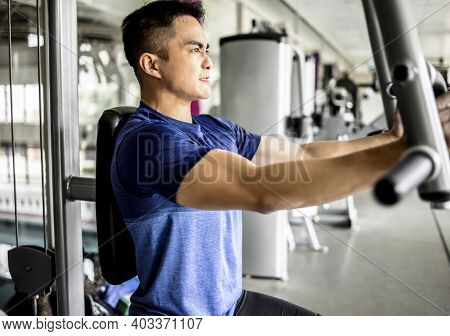 Young Man Doing Heavy Weight Exercise For Chest On Machine With Cable In The Gym