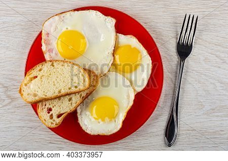 Fried Egg, Slices Of Bread In Red Glass Plate, Fork On Wooden Table. Top View
