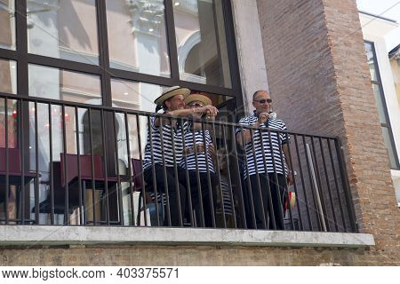 Venice, Italy - June 11, 2013: Venetian Gondoliers Drinking Coffee And Relaxing On The Balcony