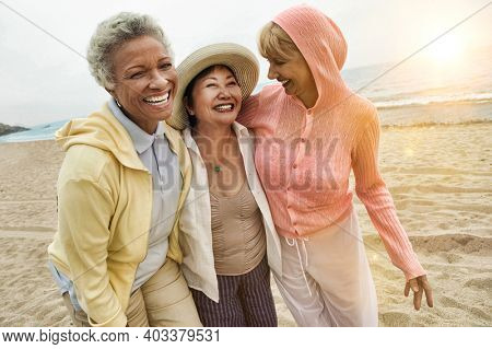 Portrait of happy multi ethnic middle aged female friends enjoying vacation at beach