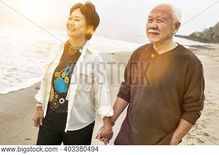 Portrait of Chinese Senior couple on beach holding hands
