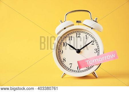 Procrastination, Delay And Postpone Concept. Sticky Note With Word Tomorrow On The White Alarm Clock