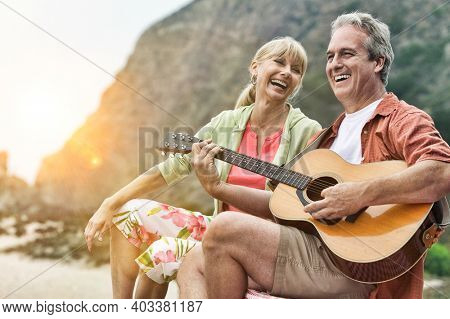 Man Playing Guitar for his wife on Beach with lens flare