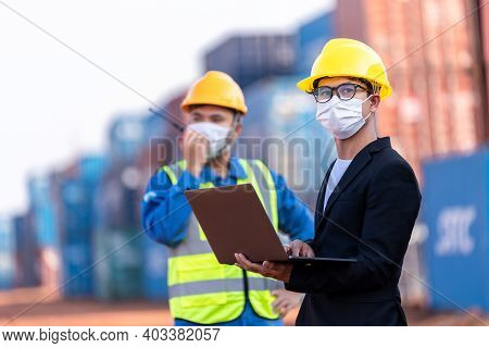 Asian Male Logistic Warehouse Foreman With Worker Using Laptop Checking List Planning And Strategy O