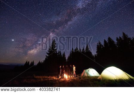 Group Of Five Tourists Are Standing Around Burning Campfire Near Two Tents Against Backdrop Pine For