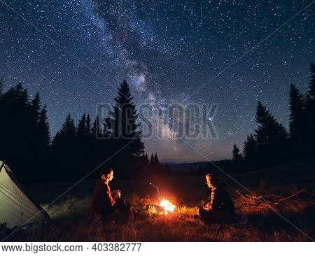 Man And Woman Communicate By Fire Against Background Of Starry Sky With Bright Milky Way. Night Camp