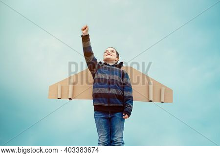 Cheerful Child Playing With Toy Wings Against Summer Sky Background Outdoors. Retro Toned. Travel, S