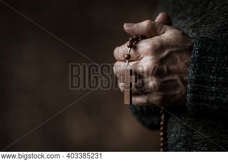 Man Holding Holy Bible And Wooden Cross
