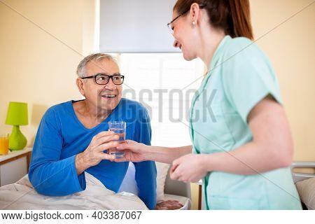 Loving Nurse Handing Glass Of Water To Her Nursing Occupant In A Elder Peoples Home, Elder People As