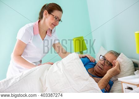 Elder Man Resident Of A Nursing Home Sleeping While Medical Staff Nurse Is Covering Him With Sheet
