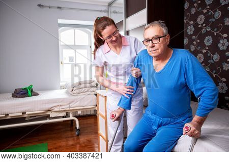 Elder Man In Nursing Home Holding A Crutch Under His Arm While Nursing Home Lady Is Assisting Him Wi