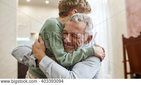 The Love Of Grandpa. Happy Grandfather Embracing His Cute Little Preschool Grandson While Standing T