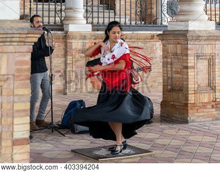 Seville, Spain - 10 January, 2021: Passionate Flamenco Dancer Woman In Colorful Clothes Dancing At T