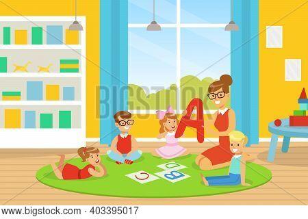 Kindergarten Teacher Explaining Alphabet To Kids, Cute Boys And Girls Learning On Floor And Learning