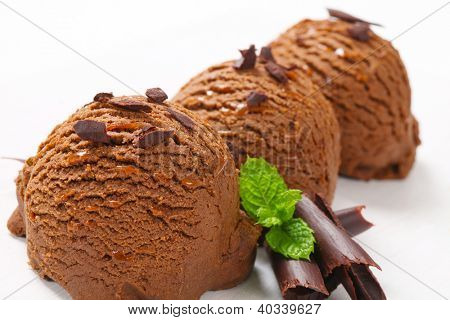 three chocolate ice cream scoops with chocolate flakes and curls