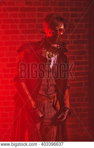 World of steampunk. Portrait of a courageous dieselpunk man in red light on a brickwall background.