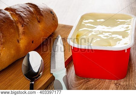 Bread, Spoon, Knife On Cutting Board, Red Box With Creamy Cheese On Wooden Table