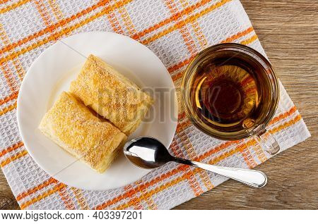 Two Puff Cookies In White Glass Plate, Teaspoon, Transparent Cup With Tea On Checkered Napkin On Bro