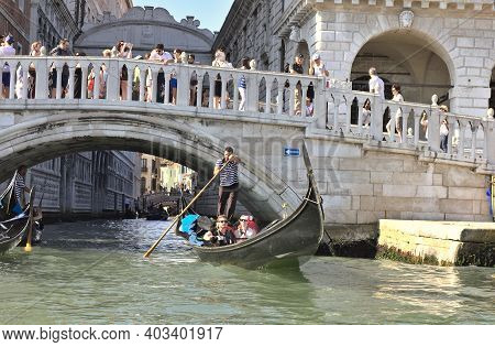 Venice, Italy - 3 August, 2016: Tourists Enjoying The Gondolas In The Canals Near The Bridge Of Sigh