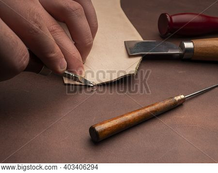 The Man Rounds The Edges Of The Leather And Next To Him Lies A Sharp Leather Knife And An Awl. Worki