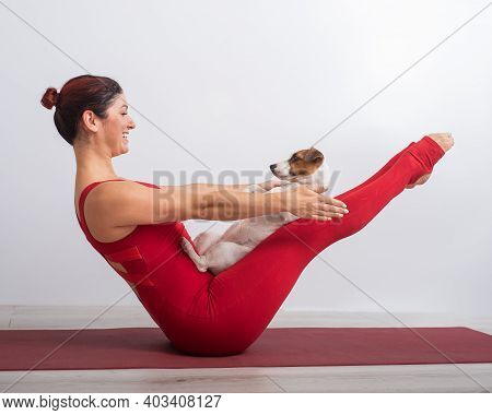 A Woman In A Red Overalls Practices Yoga With A Dog. The Girl Performs The Vi Balance Asana On A Whi