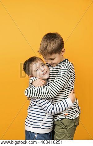 Yellow Background Studio Photograph Of Little Cute Toddler Siblings Hugging Each Other. Brothers Lov