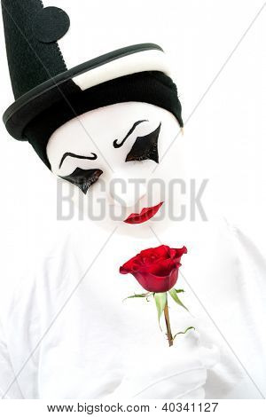 High key image of a white Pierrot clown with a red rose